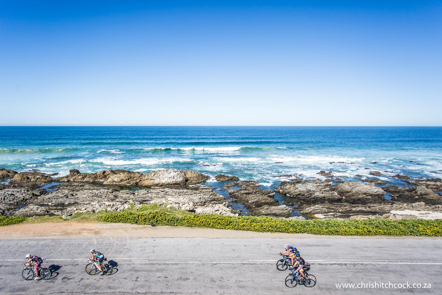 40km before the start/finish line riders battle into the head wind, known locally as the 'Beasterly Easterly'. I climbed up the dunes next to the road to get a more panoramic view of the riders and surf using a wide angle lens.